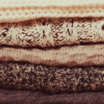 stack warm knitted sweaters in white and gray shades